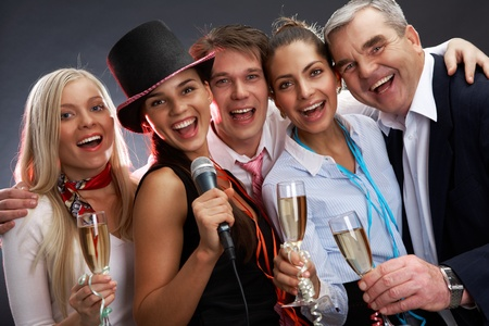 corporate woman: Photo of businesspeople with flutes of sparkling champagne singing Christmas songs Stock Photo