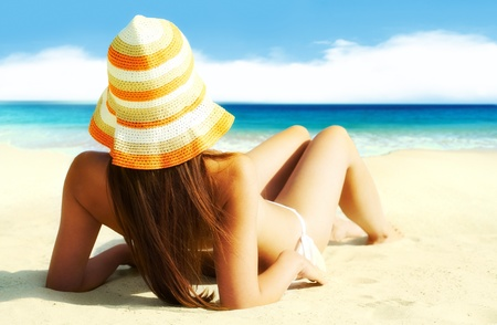 woman laying: Image of female in white bikini sunbathing on sandy beach during vacation