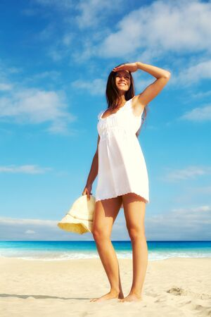 Image of female in white dress standing on sandy beach Stock Photo - 10699789