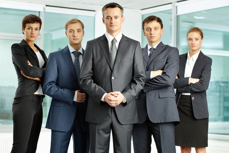 Portrait of serious business group looking at camera with confident man at foreground photo