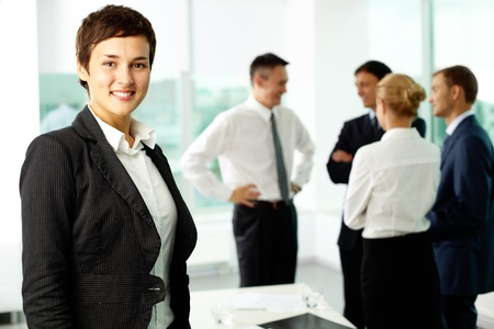 Attractive businesswoman looking at camera and smiling aginst her colleagues Stock Photo - 10699901