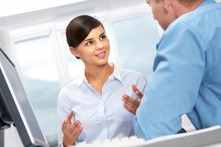 Young office worker asking her colleague  Stock Photo - 10695248