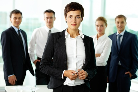 employers: Portrait of female manager against her colleagues