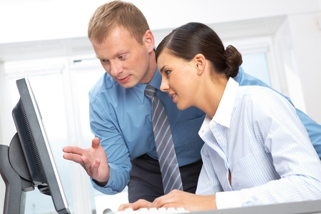 Young manager explaining something at laptop to his colleague Stock Photo - 10699760