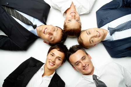 Five business people lying in floor, looking at camera and smiling Stock Photo - 10695246
