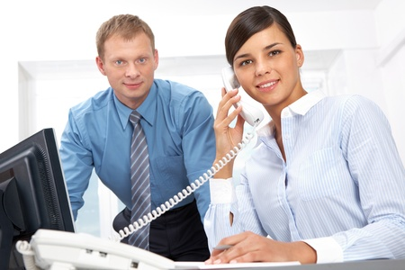 Portrait of business leader and secretary on the phone looking at camera and smiling  photo