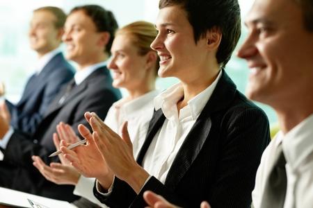 aplaudiendo: Gente de negocios sentado en una fila y aplaudiendo