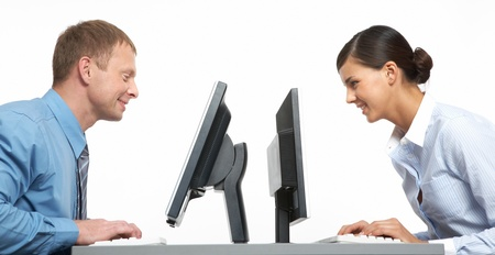 Two business colleagues sitting opposite at their monitors  Stock Photo - 10695277