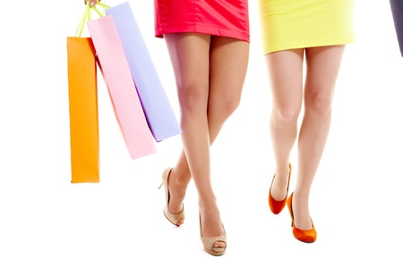heeled: Slim legs of two shopping girls isolated on white   Stock Photo