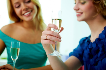 Young girl holding champagne flute in cafe, the focus is on her hand with wedding ring  photo