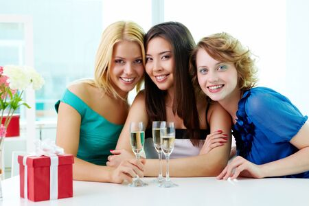 celebrating: Portrait of three girlfriends sitting in cafe, looking at camera and smiling Stock Photo