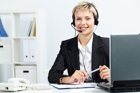 telephone headsets: Portrait of a pretty secretary sitting at computer with headset