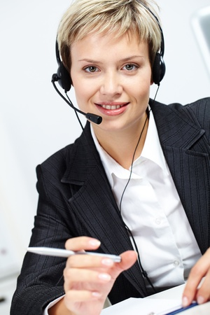 call center female: Portrait of young attractive secretary with headset looking at camera and smiling