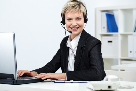 Young pretty receptionist with headset at computer looking at camera and smiling Stock Photo - 10699976