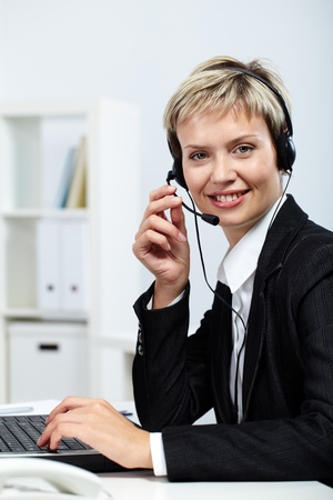 Portrait of pretty secretary answering a call and typing Stock Photo - 10700031