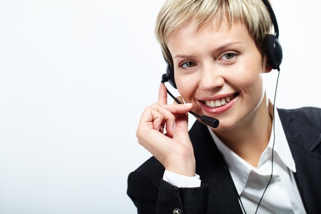 Young pretty operator with headset looking at camera and smiling isolated on white  photo
