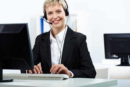 Portrait of young secretary at computer looking at camera and smiling Stock Photo - 10699992