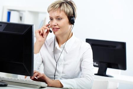 call center agent: Giovane segretaria con cuffia rispondere a una chiamata
