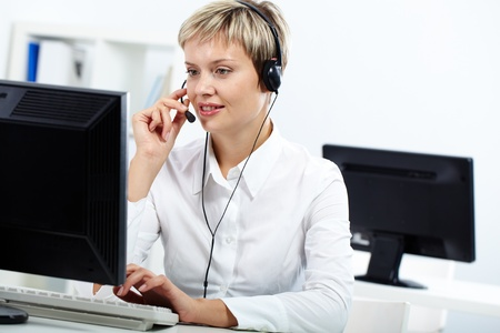 computer centre: Young secretary with headset answering a call