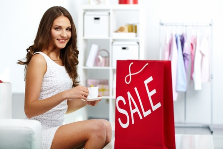 Happy shopaholic drinking coffee at shop with shopping bag from sale nearby Stock Photo - 10699914