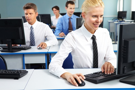 Young office worker sitting at computer and working among her colleagues  photo
