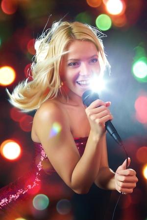 karaoke: Portrait of young beautiful girl singing    Stock Photo
