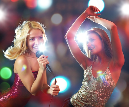 Two young beautiful girls dancing and singing photo