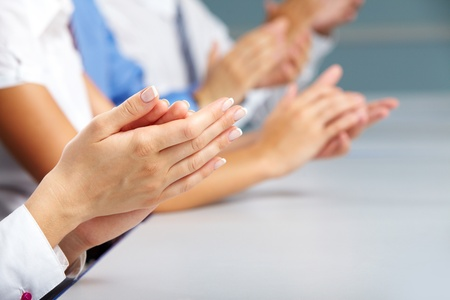 applauding: Row of clapping hands, female ones are on foreground  Stock Photo