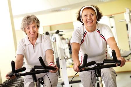 simulators: Portrait of two senior women on simulators looking at camera and smiling