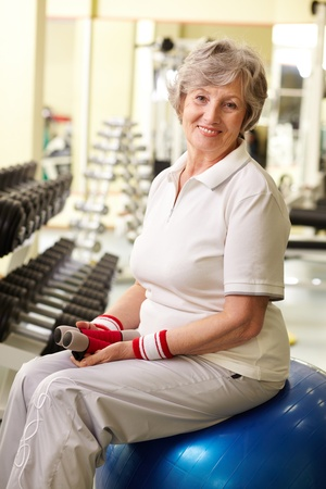 senior fitness: Portrait of senior woman looking at camera and smiling in gym Stock Photo