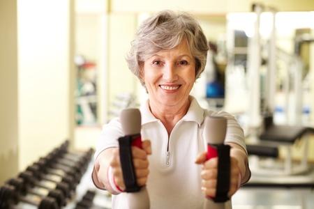 Portrait of pretty senior woman exercising with dumbbells  photo