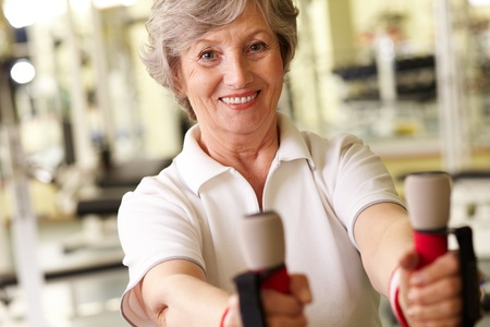one senior adult woman: Face of happy athletic woman in gym