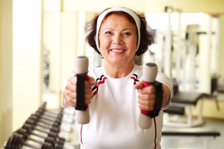 Portrait of senior woman training in gym photo
