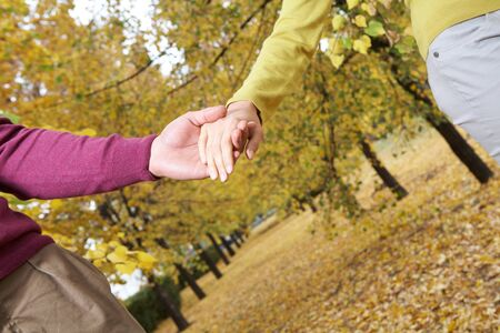 linked hands: Linked hands of couple walking in autumn