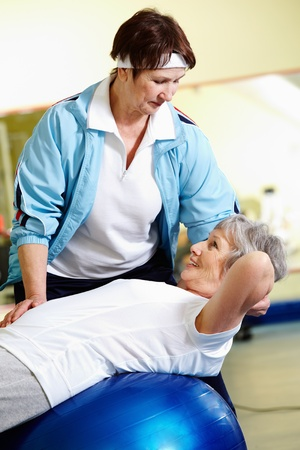 Senior woman doing abdominal exercises with her instructor in gym  photo