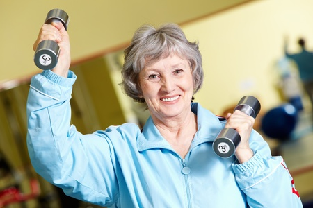elderly exercise: Portrait of positive senior woman lifting dumbbells, looking at camera and smiling Stock Photo