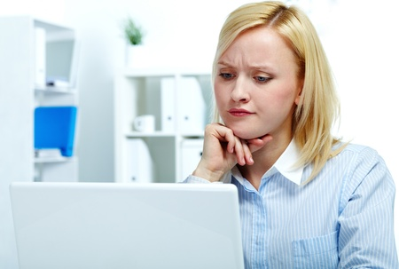 confused person: Portrait of a young woman sitting at computer and grimacing  Stock Photo