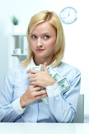 corporate greed: Portrait of a young woman clasping dollars to her bosom