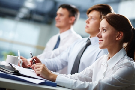interviewing: Three business people sitting at seminar, the focus is on woman Stock Photo