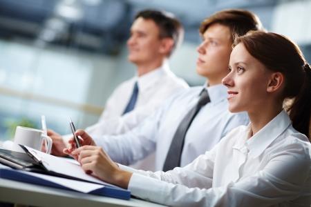 Tres personas de negocios sentado en el seminario, la atención se centra en la mujer Foto de archivo