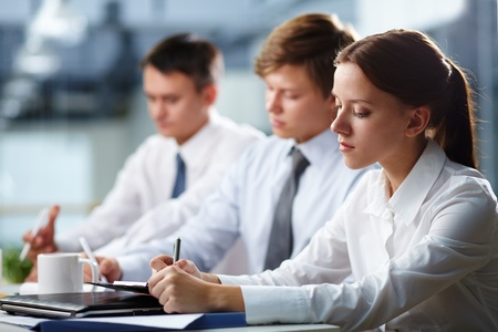 employee training: Three young people making notes at lecture  Stock Photo