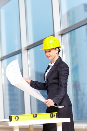 A young woman architect in helmet examining a plan  photo