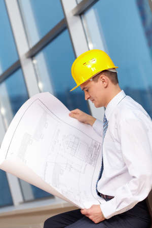 A young architect in helmet looking at blueprint  photo