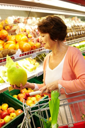 Image of senior woman choosing products in supermarket with cart near by photo