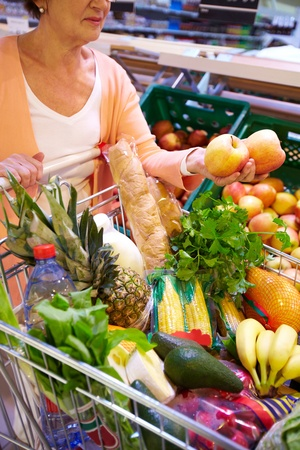 choose person: Image of senior woman with fresh vegetables and fruits in cart