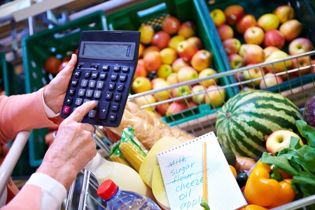 Image of senior woman hand touching buttons of calculator with goods in cart near by photo