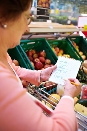 Image of senior woman looking at product list with goods in cart near by photo