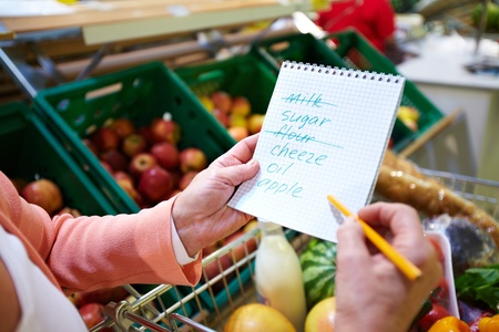 grocery cart: Image of senior woman hands holding product list with goods in cart near by Stock Photo
