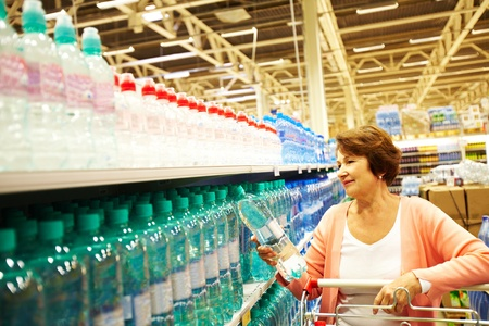 Image of mature customer choosing water from big assortment in a shop photo