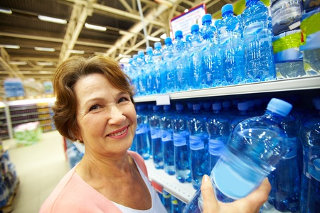 Image of mature customer holds bottle of pure water photo